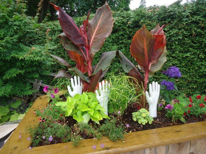 cannas with helping hands, whimsy, garden art
